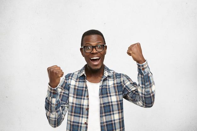 Mensen, succes, prestatie en overwinningsconcept. succesvolle jonge afro-amerikaanse student schreeuwend van opwinding, balde vuisten
