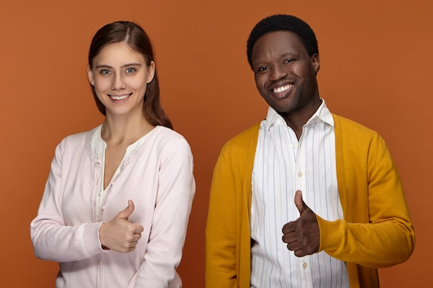Mensen, succes, tekens en gebarenconcept. succesvolle vriendelijk ogende zelfverzekerde jonge zwarte mannelijke en blanke vrouw, duimen opdagen gebaar, genieten van samenwerken in team, gelukkig lachend