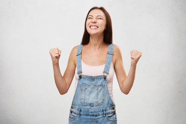 Mensen, succes, winnen, overwinning, opwinding, doelen, vastberadenheid en prestatieconcept. blij opgewonden gelukkige studentenvrouw die toejuicht, succes viert, ja schreeuwt met gebalde vuisten