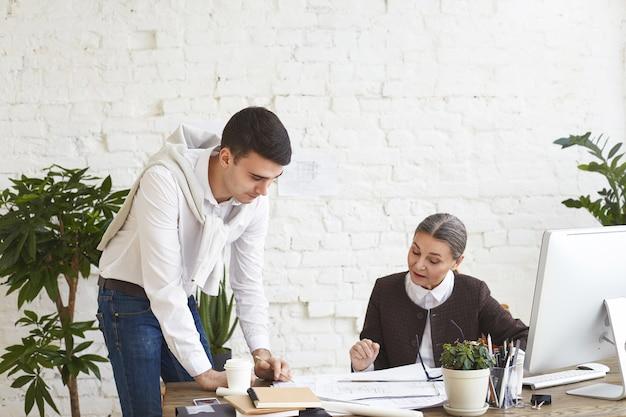Mensen, teamwerk, samenwerking en baanconcept. aantrekkelijke jonge mannelijke architect die zich bij bureau bevindt dat potlood houdt terwijl technische tekeningen aan zijn vrouwelijke werkgever van middelbare leeftijd in modern bureauinterieur worden getoond