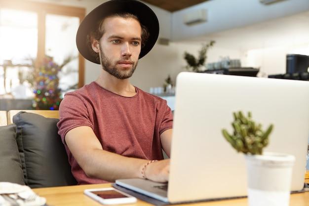 Mensen, technologie en communicatieconcept. ernstige bebaarde freelancer in stijlvolle hoed die voor een open laptop zit en op afstand werkt, met behulp van een gratis snelle internetverbinding in een café
