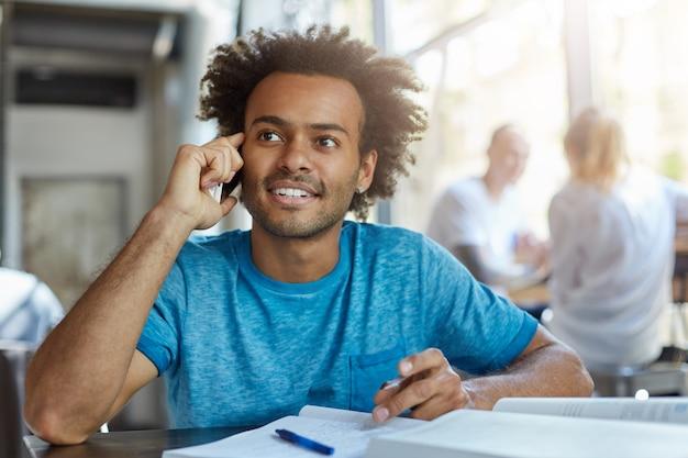 Mensen, technologie en communicatieconcept. knappe afro-amerikaanse student met baard glimlachen, met mooi telefoongesprek