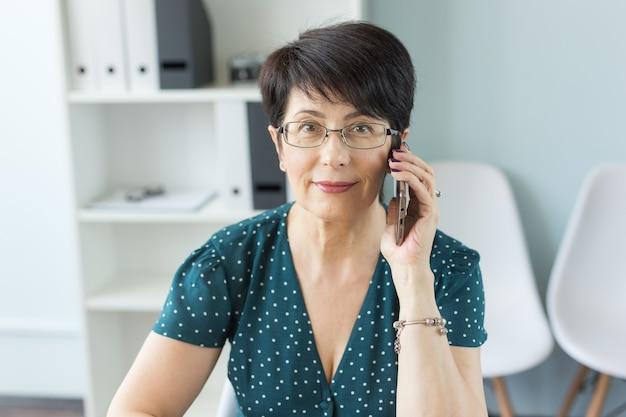 Mensen, technologie en communicatieconcept - volwassen bedrijfsdame die telefonisch in bureau spreekt.