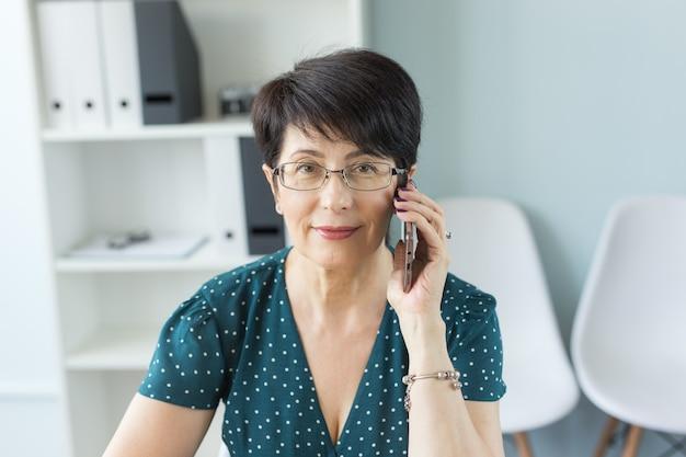 Mensen, technologie en communicatieconcept - vrouw die van middelbare leeftijd smartphone uitnodigen