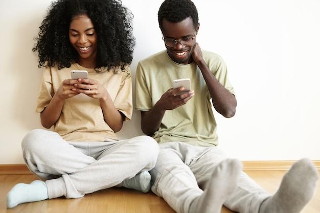 Mensen, technologie en vrije tijd concept. gelukkig modern paar dat vrijetijdskleding draagt die met snelle internetverbinding op elektronische apparaten, vrolijk kijkt