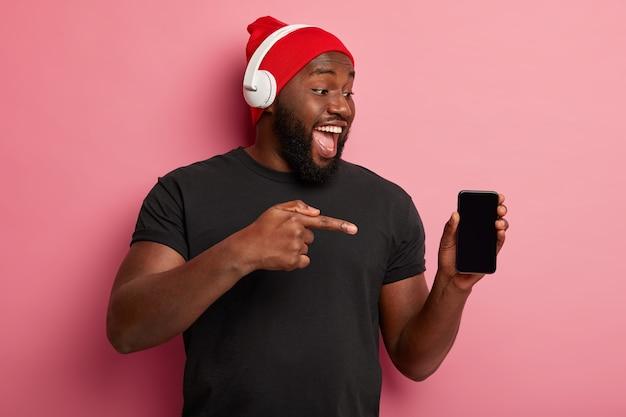 Mensen, technologie, levensstijl en reclameconcept. gelukkig donkere man toont leeg scherm van smartphoneapparaat