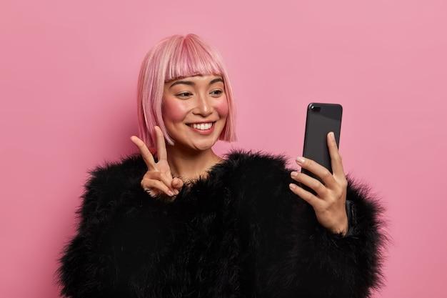 Mensen, technologie, levensstijlconcept. glimlachende blij roze harige vrouw draagt pluizige zwarte trui, neemt selfie, toont v-teken of vredesgebaar, stuurt goede positieve vibes, geniet van online videogesprek