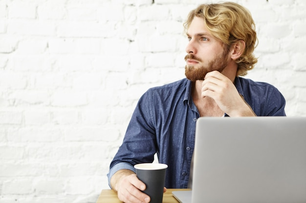 Mensen, technologieën en online communicatie. knappe bebaarde man met blond haar met behulp van wifi op laptop tijdens koffiepauze in café, zittend aan witte bakstenen muur met kopie ruimte voor uw inhoud