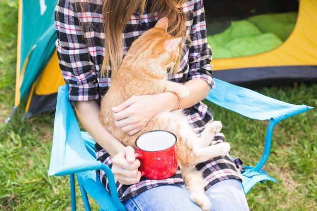 Mensen toerisme en natuur concept vrouw in zonnebril een kat zitten in de buurt van de tent aaien
