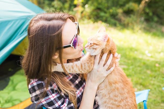 Mensen, toerisme en natuurconcept - vrouw die in zonnebril een kat houdt die dichtbij de tent zit