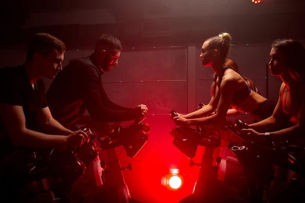 Mensen trainen, benen cardiotraining op de fiets in de fitnessruimte, competitie houden, voor een goede gezondheid. bodybuilder, levensstijl, fitness, training en sport trainingsconcept