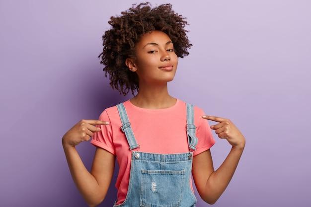 Mensen, trots, arrogantie concept. zelfverzekerde trotse vrouw heeft afro-kapsel tevreden met eigen hoge prestaties, voelt zich zelfverzekerd