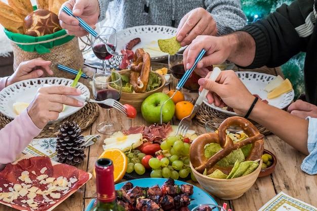 Mensen uit de familiegroep genieten samen van een lunch in het seizoen van kerstdagen