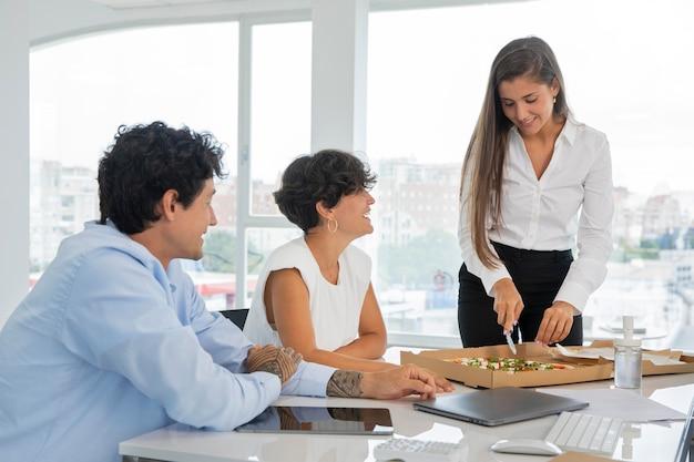 Mensen uit het bedrijfsleven aan het werk met pizza medium shot