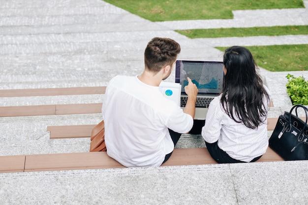 Mensen uit het bedrijfsleven analyseren grafiek op laptop scherm wanneer ze buiten zitten, uitzicht vanaf de achterkant