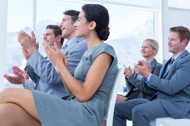 Mensen uit het bedrijfsleven applaudisseren tijdens een vergadering