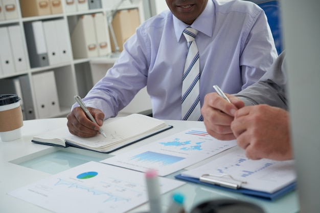 Mensen uit het bedrijfsleven bespreken grafieken en rapporten en ontmoeten en maken aantekeningen in planner