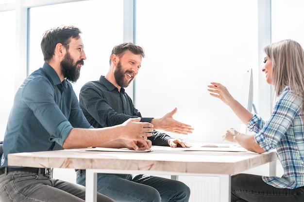 Mensen uit het bedrijfsleven bespreken iets zittend aan de kantoortafel. kantoor weekdagen