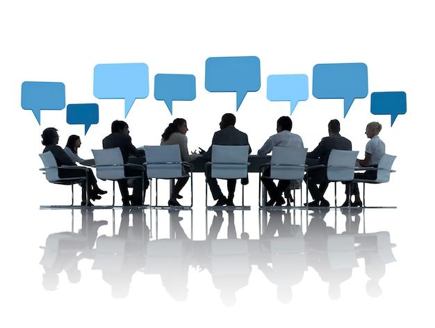 Mensen uit het bedrijfsleven bespreken rond de conferentietafel en tekstballonnen boven hen.