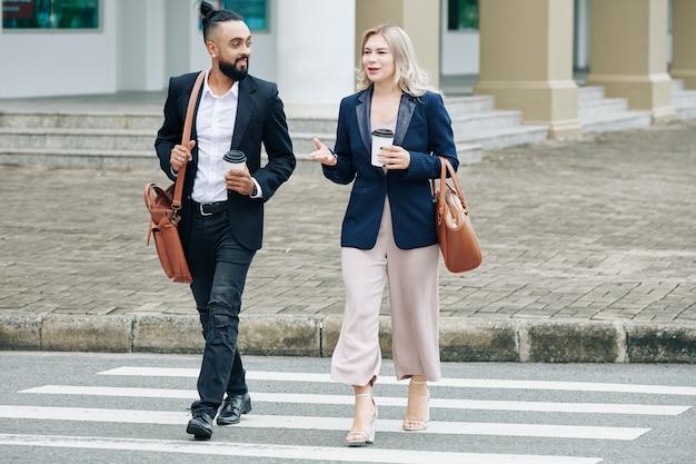 Mensen uit het bedrijfsleven die afhaalkoffie drinken bij het oversteken van de weg en het bespreken van nieuws