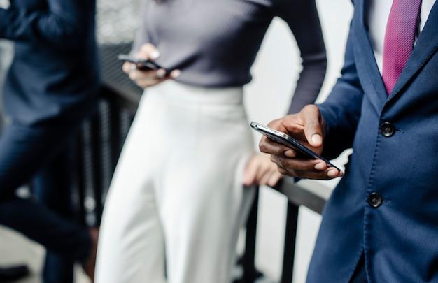 Mensen uit het bedrijfsleven die terloops smartphones buiten gebruiken