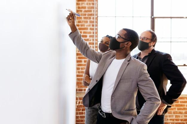 Mensen uit het bedrijfsleven dragen maskers brainstormen