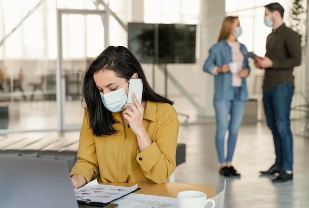 Mensen uit het bedrijfsleven dragen medische maskers op het werk