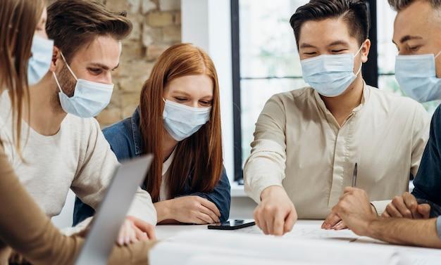 Mensen uit het bedrijfsleven dragen medische maskers tijdens het bespreken van een project