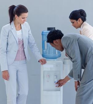 Mensen uit het bedrijfsleven drinken uit een waterkoeler