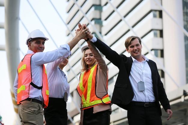 Mensen uit het bedrijfsleven en ingenieur geven elkaar de groeten van vijf als eenheidsgroep