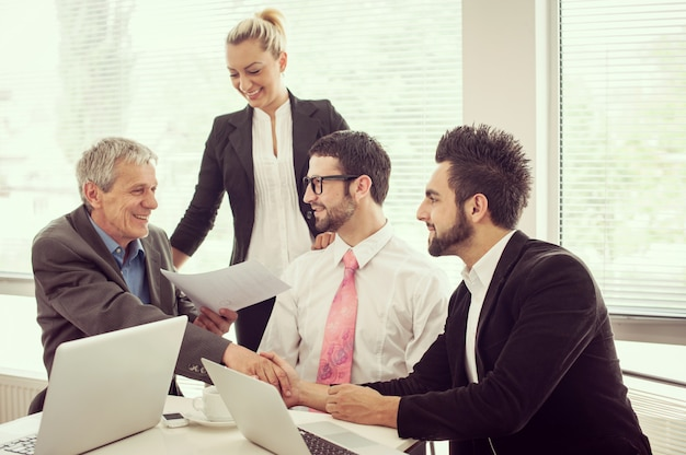 Mensen uit het bedrijfsleven en leidinggevenden met vergadering met behulp van laptop
