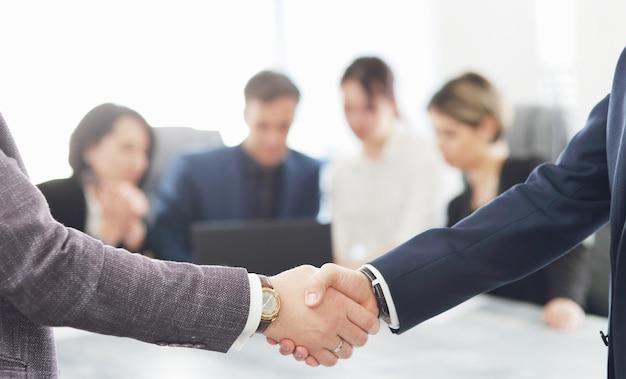 Mensen uit het bedrijfsleven handen schudden bij het afronden van een vergadering