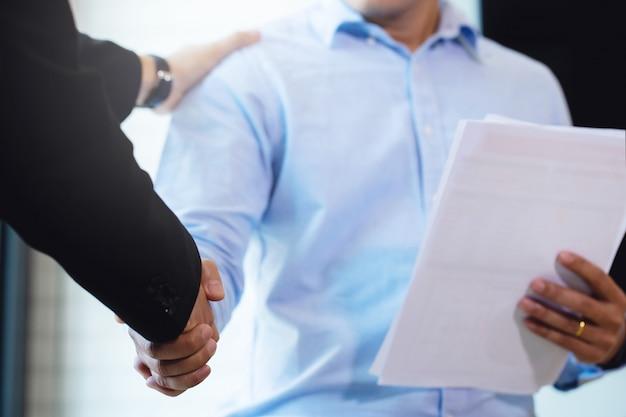 Mensen uit het bedrijfsleven handen schudden, een vergadering afronden. handdruk van gelukkige mensen uit het bedrijfsleven na contractovereenkomst