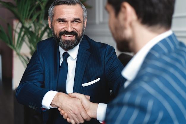 Mensen uit het bedrijfsleven handen schudden, een vergadering afronden.