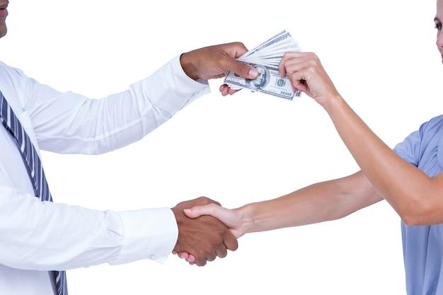Mensen uit het bedrijfsleven handen schudden en bankbiljetten uitwisselen
