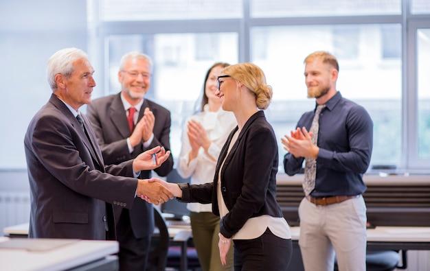 Mensen uit het bedrijfsleven handen schudden na succesvolle onderhandelingen op kantoor