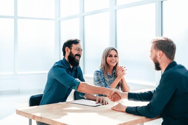 Mensen uit het bedrijfsleven handen schudden tijdens het interview