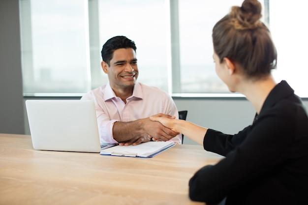 Mensen uit het bedrijfsleven handen schudden tijdens vergadering