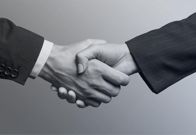 Mensen uit het bedrijfsleven handenschudden tijdens vergadering, zwart-wit foto