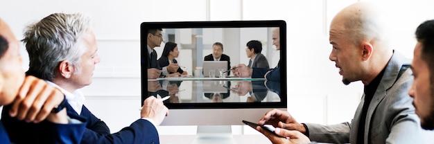 Mensen uit het bedrijfsleven hebben een conferentievergadering met behulp van een computerschermmodel
