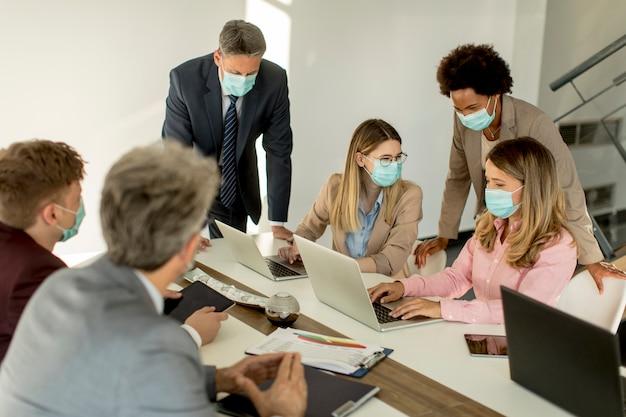 Mensen uit het bedrijfsleven hebben een vergadering en werken op kantoor en dragen maskers als bescherming tegen het coronavirus