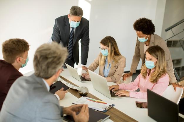Mensen uit het bedrijfsleven hebben een vergadering en werken op kantoor en dragen maskers als bescherming