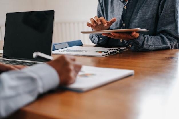 Mensen uit het bedrijfsleven hebben een vergadering, zakenman werken met team met behulp van tablet