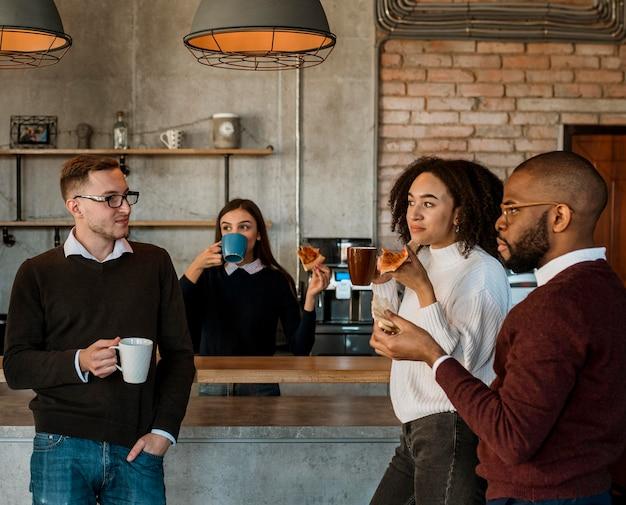 Mensen uit het bedrijfsleven hebben pizza en koffie tijdens een kantoorvergadering pauze