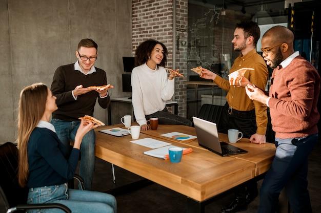 Mensen uit het bedrijfsleven hebben pizza tijdens een kantoorvergadering pauze
