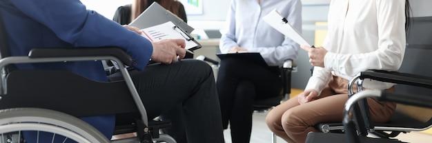Mensen uit het bedrijfsleven houden een vergadering van een van de aanwezigen in een rolstoel