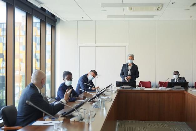 Mensen uit het bedrijfsleven in beschermende maskers bespreken nieuw businessplan samen tijdens bijeenkomst op kantoor