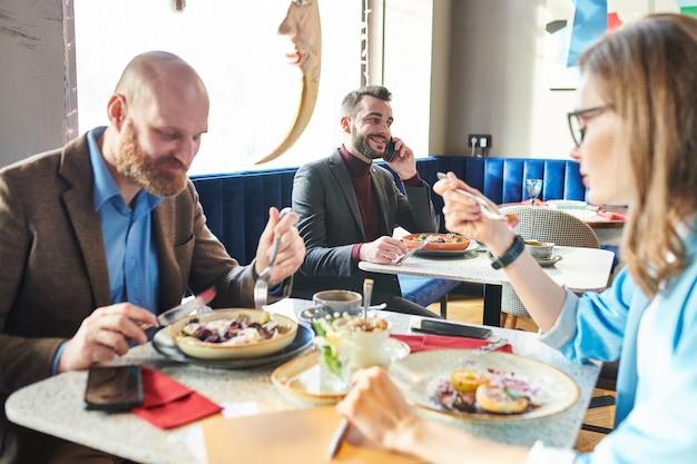 Mensen uit het bedrijfsleven in café: succesvolle jonge zakenman salade eten en zaken bespreken op telefoon terwijl collega's samen lunchen