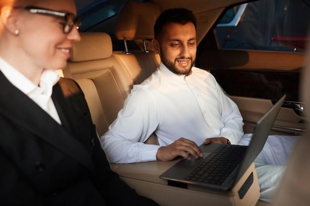 Mensen uit het bedrijfsleven in de auto zitten en samen laptop gebruiken tijdens het rijden