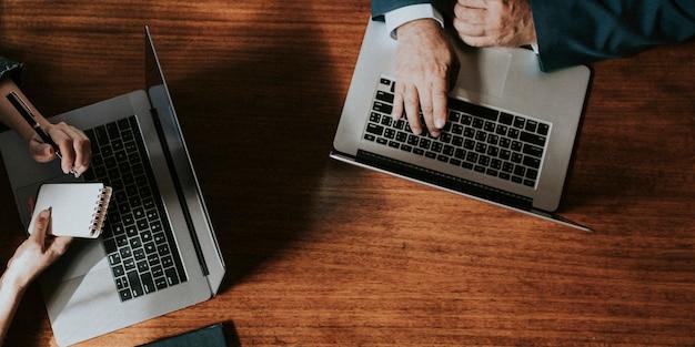 Mensen uit het bedrijfsleven in een vergadering met behulp van hun laptops